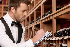 Confident sommelier. Side view of confident young sommelier writing something at his note pad and looking at the wine bottles stock photo