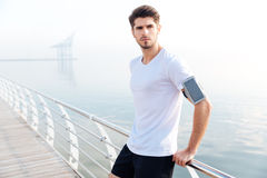 Confident sportsman with cell phone on armband standing at pier. Portrait of confident young sportsman with cell phone on armband standing on pier Stock Photo