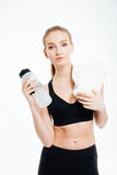 Confident sportswoman standing with bottle of water and white towel Royalty Free Stock Photos