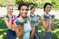 Confident sporty women lifting hands weights Royalty Free Stock Photography