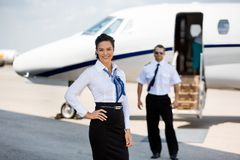 Confident Stewardesses Smiling With Pilot And Stock Images