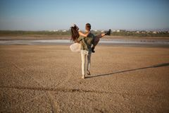 Romantic couple on a natural background. Boyfriend holding girlfriend in hands. Romance concept. Copy space. Stock Photos
