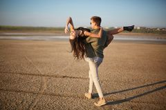 Romantic couple on a natural background. Boyfriend holding girlfriend in hands. Romance concept. Copy space. Royalty Free Stock Photos