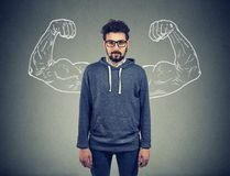 Confident strong man hipster on wall background. Strong confident young man hipster in glasses flexing his muscles royalty free stock images