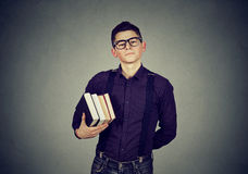Confident student carrying books wearing glasses. Confident smart student carrying books wearing glasses Royalty Free Stock Photography