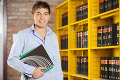 Confident Student Holding Books While Standing In. Portrait of confident male student holding books while standing in university campus Royalty Free Stock Images