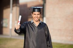 Confident Student Showing Diploma On Graduation Royalty Free Stock Photo