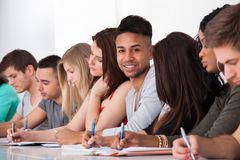 Confident student sitting with classmates writing at desk. Portrait of confident college student sitting with classmates writing at desk in classroom Stock Photos