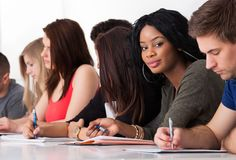Confident student sitting with classmates writing at desk. Portrait of confident female college student sitting with classmates writing at desk Stock Photography