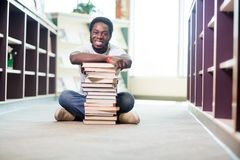 Confident Student With Stacked Books Sitting In. Full length portrait of confident young student with stacked books sitting on floor at library Royalty Free Stock Photos