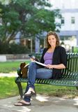 Confident Student Studying On Bench At Campus Stock Photo