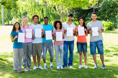 Confident students holding blank papers Stock Image