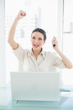 Confident stylish brunette businesswoman raising her fist Stock Images