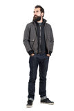 Confident stylish hipster wearing jacket over hooded sweatshirt looking away with hands in pockets. Full body length portrait isolated over white studio Stock Photography