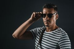Confident stylish man posing in striped t-shirt and sunglasses. Isolated on grey stock image
