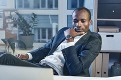 Confident stylish man is working in office thoughtfully. Lost in thoughts. Portrait of serious calm young african businessman in suit is sitting at workplace and Stock Image