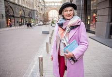 Confident stylish mature lady posing with fashionable journal. Portrait of happy senior woman standing on street with lots of boutiques. She is holding magazine stock images