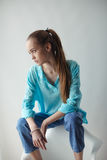 Confident stylish urban young woman looking away while sitting on chair, on gray background Stock Photo