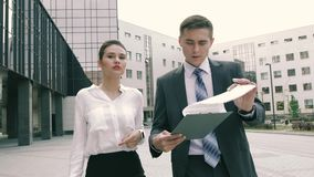 Confident and successful business partners doing business outdoors on their way to work stock video footage