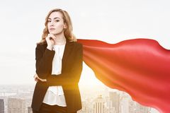 Superwoman businesswoman finance superhero, city. Confident and successful businesswoman wearing a suit and a red cape standing against a morning cityscape Stock Image