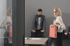 Confident and successful colleagues at work. Paperwork before deal. Woman and bearded man in office background. Business. Confident and successful colleagues at Royalty Free Stock Photos