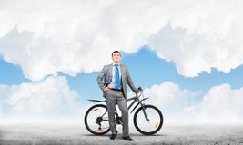 Confident and successful man in business suit. Standing with bike. Businessman with bicycle on background of blue sky. Male cyclist posing on camera with royalty free stock photos
