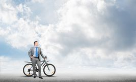 Confident and successful man in business suit. Standing with bike. Businessman with bicycle on background of blue sky. Male cyclist posing on camera with royalty free stock photography