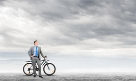 Confident and successful man in business suit. Standing with bike. Businessman with bicycle on background of blue sky. Male cyclist posing on camera with stock photo