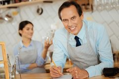 Confident successful man standing in the kitchen and making notices. Royalty Free Stock Photo