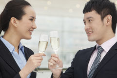 Confident and successful young business people toasting with champagne flutes Stock Photos
