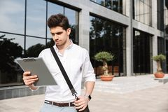 Confident successful young businessman. Dressed white shirt working outdoors, holding tablet, noting stock images
