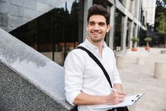 Confident successful young businessman. Dressed white shirt working outdoors, holding tablet, noting royalty free stock photos