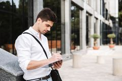 Confident successful young businessman. Dressed white shirt working outdoors, holding tablet, noting royalty free stock image