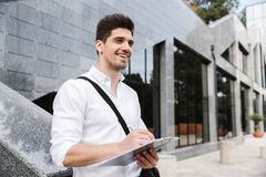 Confident successful young businessman. Dressed white shirt working outdoors, holding tablet, noting stock photo