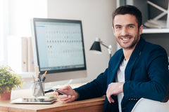 Confident and successful. Confident young man holding smart phone and smiling while sitting at his working place in office Stock Photo