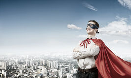 Confident super hero. Young super hero man in mask with arms crossed on chest Royalty Free Stock Image
