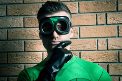 Confident superhero against a brick wall Stock Photography