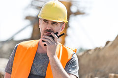 Confident supervisor using walkie-talkie at construction site Royalty Free Stock Photos