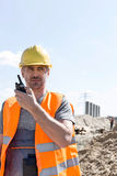 Confident supervisor using walkie-talkie at construction site against sky Stock Image