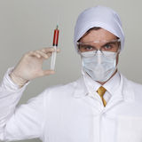Confident surgeon holding a syringe. Against a white background Stock Photo