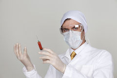 Confident surgeon holding a syringe. Against a white background Stock Photography