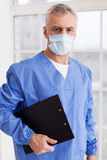 Confident surgeon. Senior grey hair doctor in surgical mask holding a clipboard and looking at camera Royalty Free Stock Photos