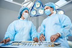 Confident surgeons looking at each other while working stock photo
