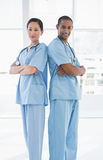 Confident surgeons standing back to back in hospital Stock Images