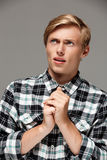 Confident surprised blond handsome young man wearing casual plaid shirt with hands ready to pray looking up, copy space. Confident surprised blond handsome young Stock Photo