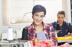 Confident Tailor Sitting At Workbench In Sewing Factory. Portrait of confident female tailor sitting at workbench with colleague working in background at sewing Royalty Free Stock Photo