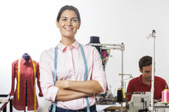 Confident Tailor Standing Arms Crossed In Factory. Portrait of confident tailor standing arms crossed in factory with employee working in background Royalty Free Stock Photos
