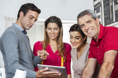 Confident Tailor Standing With Colleagues Using Tablet Computer Stock Photography