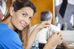 Confident Tailor Threading Needle Of Sewing Machine Royalty Free Stock Photos