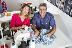 Confident Tailors Sitting At Workbench. High angle portrait of confident tailors sitting at workbench in sewing factory Royalty Free Stock Image